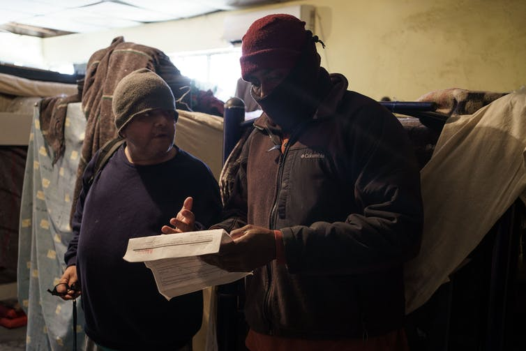 Two men in winter clothing in a room of bunk beds discuss a piece of paper that one man is holding