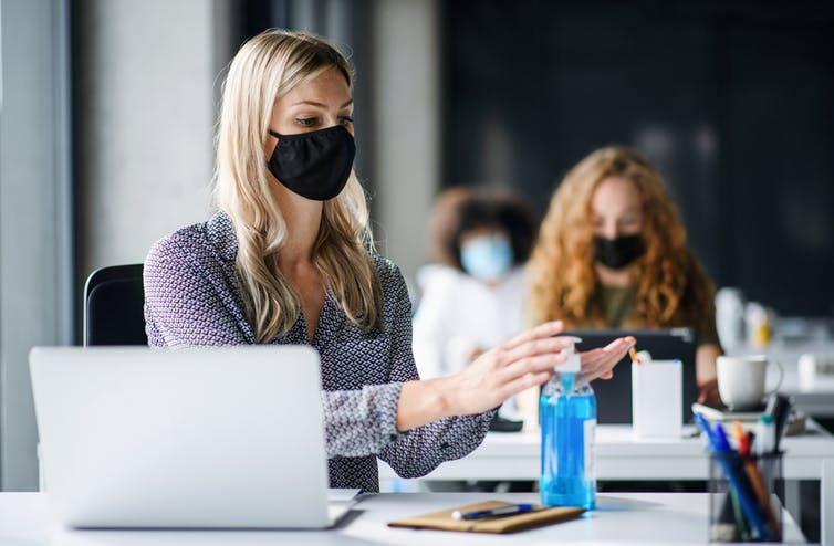 Office workers wearing masks, one santising hands