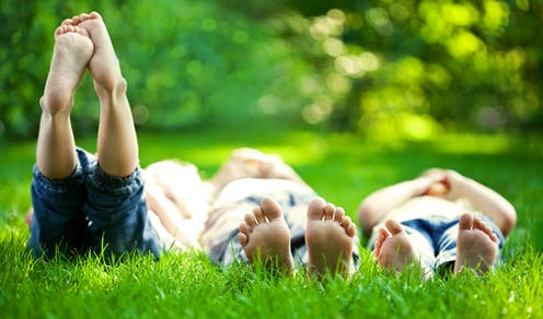 People relaxing on grass in a park