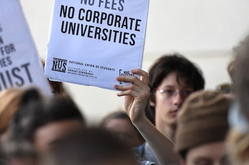 Student holding sign 'NO CORPORATE UNIVERSITIES' at protest