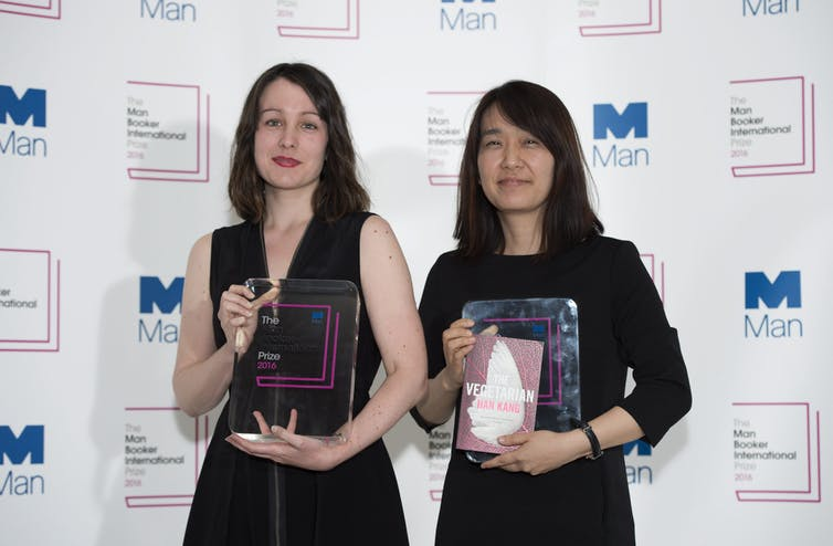 A white woman and an Asian woman pose with trophies.