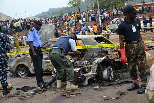 Men in police and military uniforms inspecting car wreckage left on the street following a bomb blast