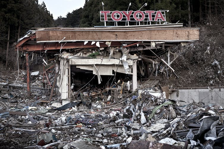 A Toyota sign hanging over a pile of rubble, caused by the Fukushima disaster.