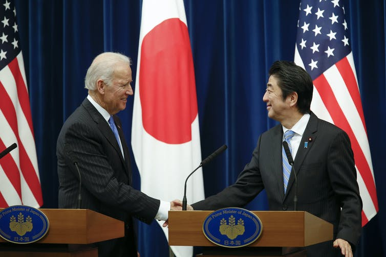 The then US vice president Joe Biden shakes hands with Japanese prime minister Shinzo Abe at a meeting in Tokyo, 20131. In the background are US and Japanese flags.