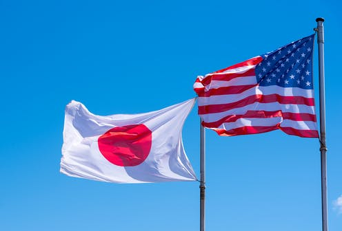 Japanese and US flags flying side-by-side.