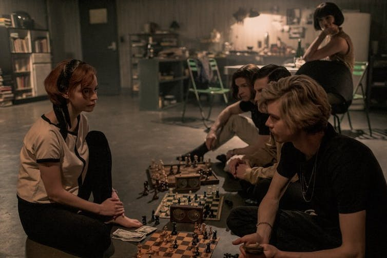 A young woman in front of a line of young men playing chess.
