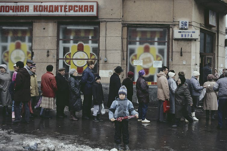 Dozens of people in Moscow stand in a food line on an icy street waiting to buy bread