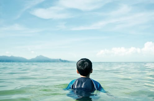 Rear view of a boy sitting in the ocean.