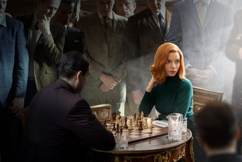 A woman playing chess surrounded by men.