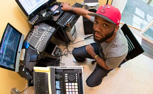A man wearing a baseball cap sits in front of a computer and music studio equipment in a small room