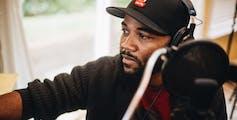 A man records an album next to a microphone.