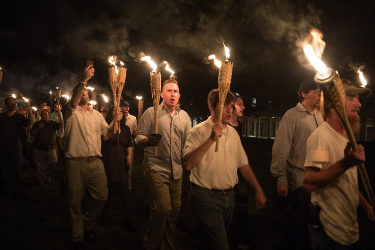 Torch-bearing white men marching at night, shouting