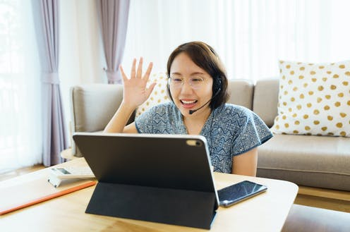 Mature student waves as she talks online using a laptop