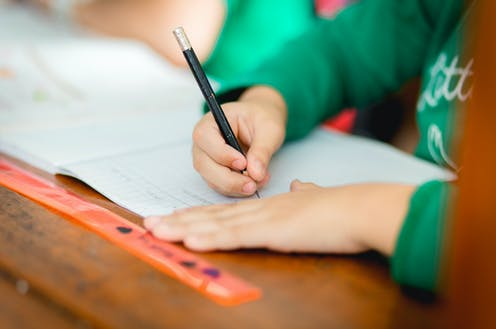 Child's hands writing in school exercise book
