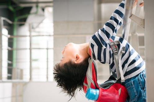 Hyperactive boy climbing ladder wearing backpack