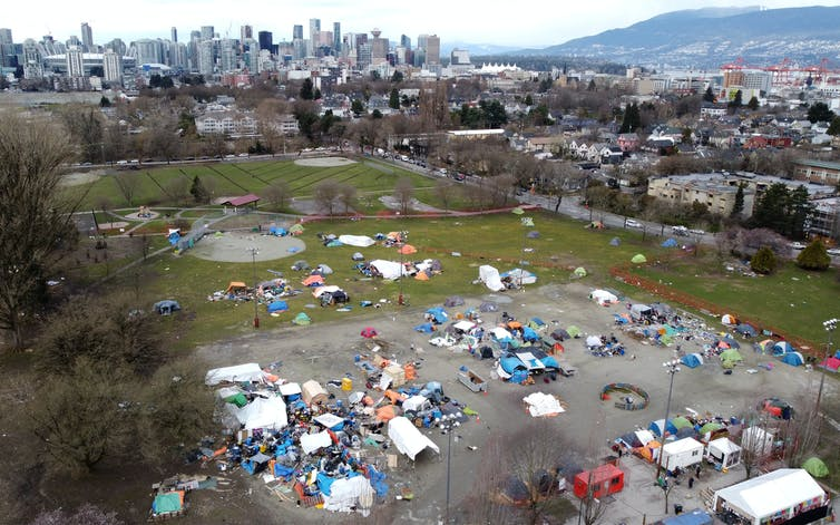 A group of tents and temporary structures in a park, shot from above