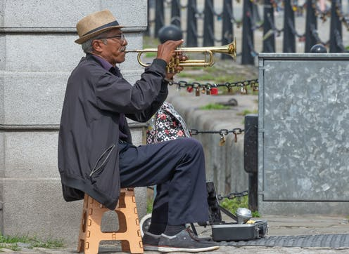 A seated trumpeter busks in Liverpool.