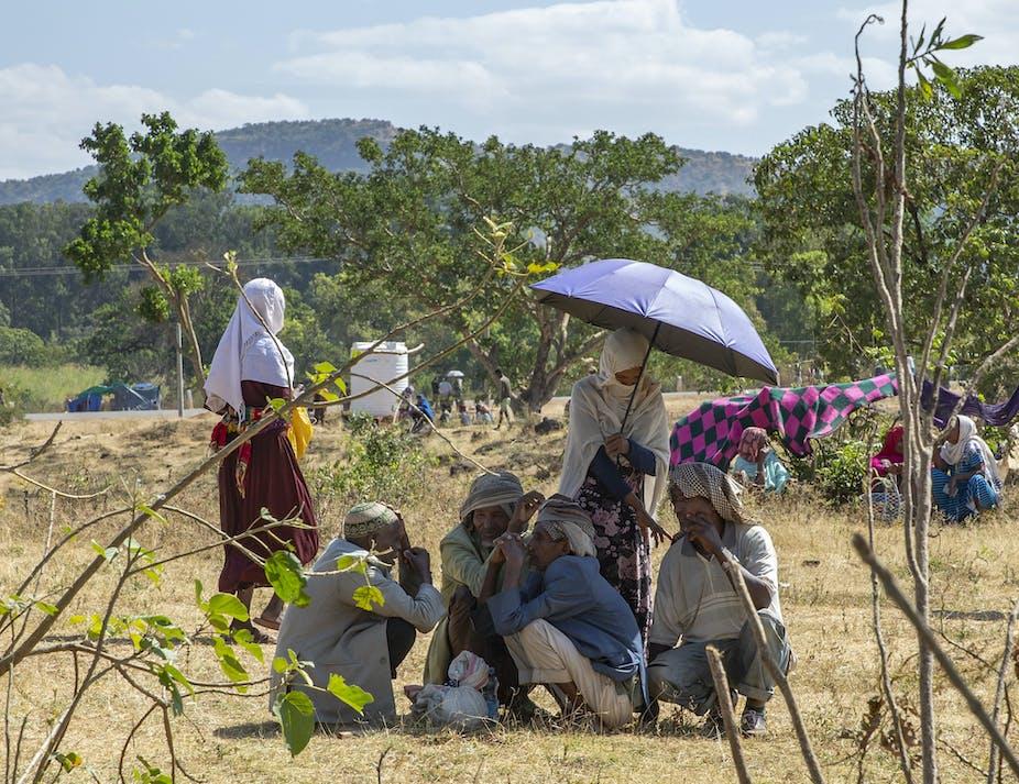 Men and women huddled under an umbrella