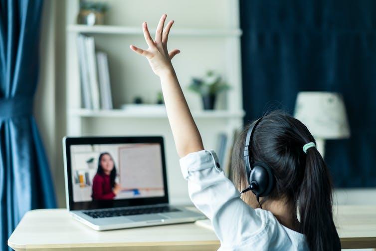Child at laptop wearing headphones raises her hand