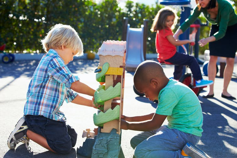 young children playing with a toy in a playground
