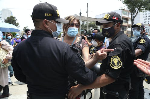 A woman in a mask is stopped by two police officers wearing masks.