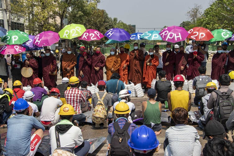Men in hardhats sit on the ground facing monks in robes holding colorful umbrellas