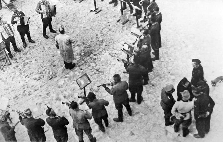 Performers form a circle around a man as guards observe.