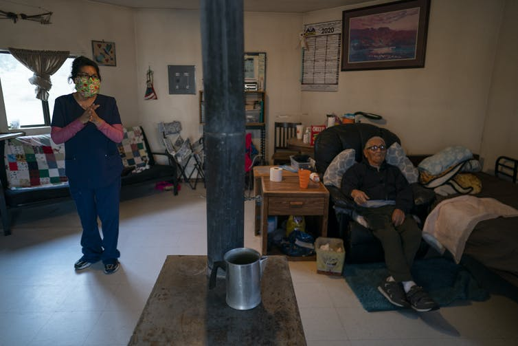 A woman and her uncle in a home with a stove for heating.