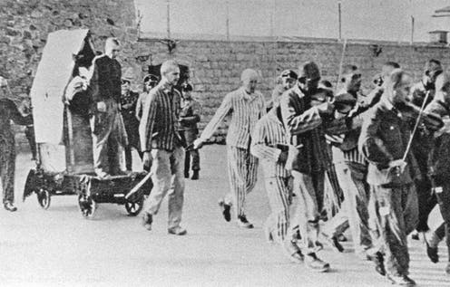 A group of prisoners march and play instruments as they lead a boy to execution.