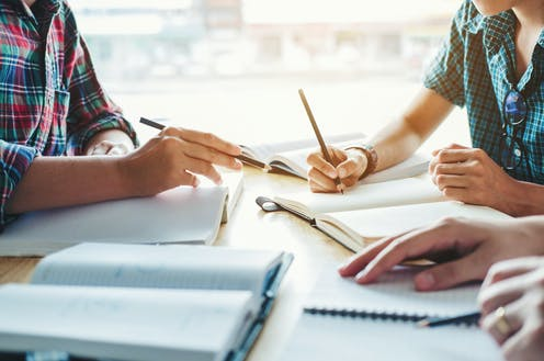 tres personas con sendos lapiceros ante cuadernos en blanco.