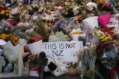 Bouquets of flowers piled up at a memorial