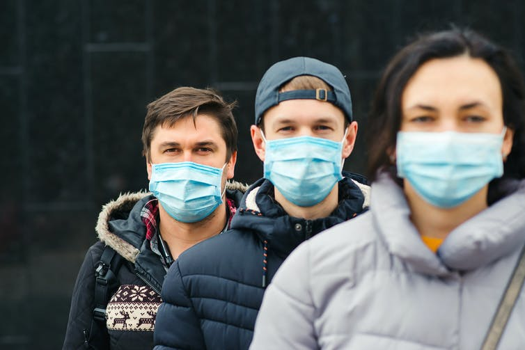Three young people in masks