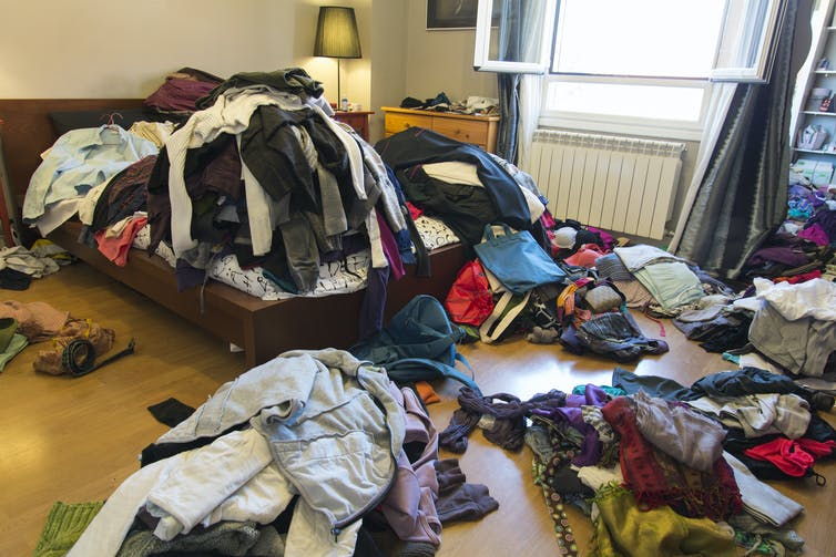 A room with clothes on the floor and piled high on the bed.