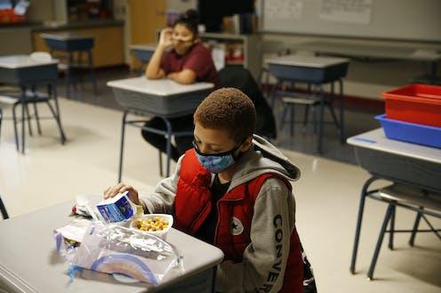 A school boy wearing a mask eats breakfast at his desk.