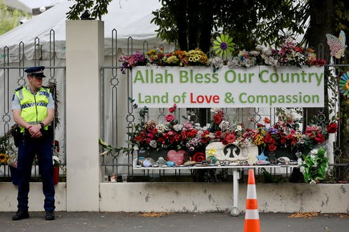 Police officer outside gate with sign reading 'Allah bless our country'