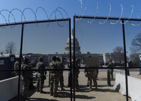 Soldiers and barbed wire block the way to the US Capitol