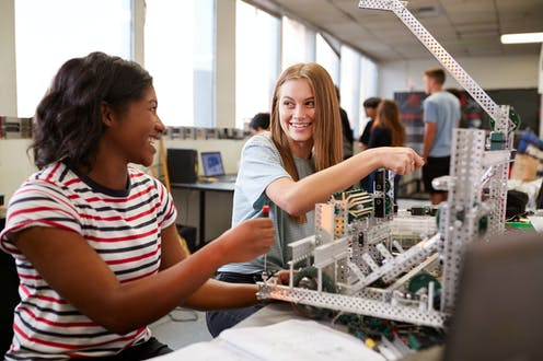 Two female students looking happy in a robotics class