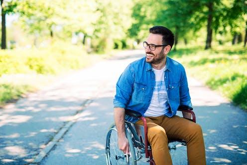 Man in wheelchair in park smiling