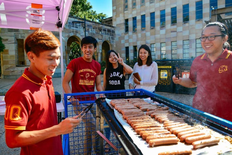 students look at sausages being barbecued