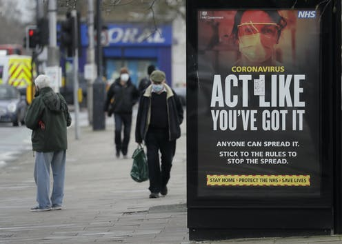 People walking wearing masks in London, next to a sign saying 'act like you've got it'.