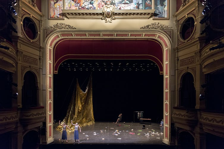 A wide shot of a proscenium arch. Two women look tiny against a messy stage.