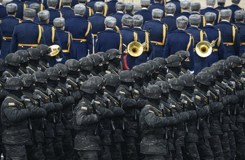 Troops march beside a military band.