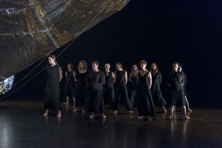 A mass of women in black dresses.