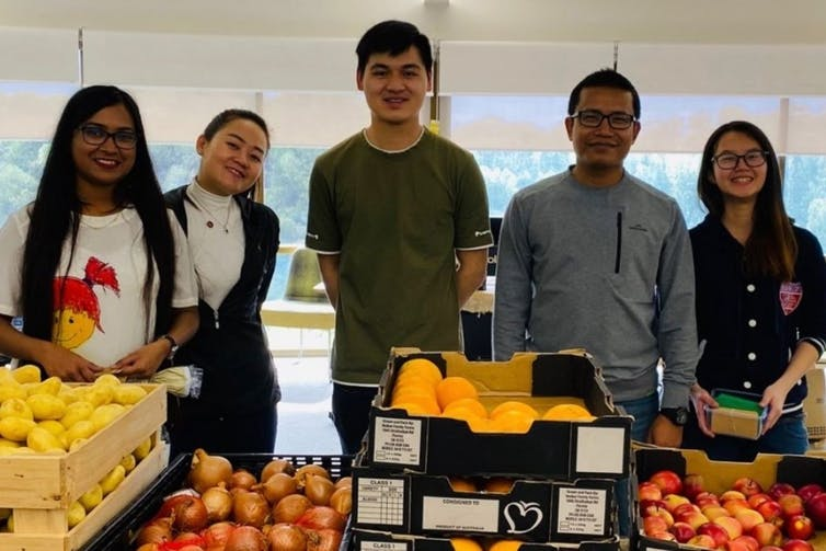 university students at a fresh produce market stall