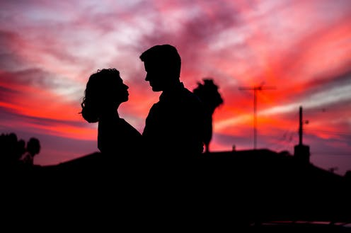 young couple embrace with sunset behind