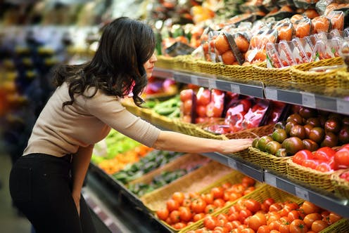 young woman looking at display of fruit in shop