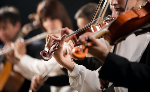 A blurred picture of people playing in an orchestra.