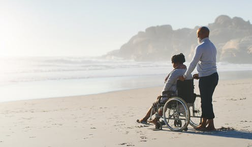 A woman sitting on a wheelchair with a man behind her holding the chair's handles. They're at a beach.