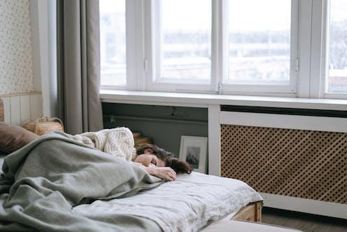 'Mujer durmiendo de día con una ventana de fondo'