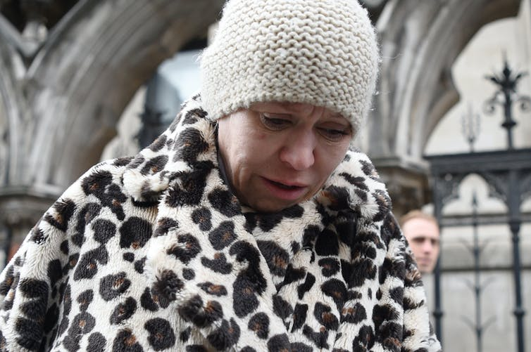 A woman in a beanie hat and a faux leopard-skin coat looking upset as she leaves the High Court in London.